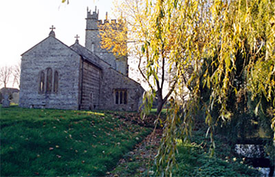 View of church from the banks of the River Piddle.