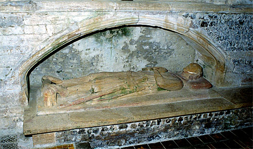 In a tomb recess in the chapel is this effigy of a man clad in a long military style surcoat, tippet and hood. Feet spurred and resting on a dog or a lion. At left side a dagger and a sword slung from belt buckled over hips. Late 13th century but the face has been restored at some later date.
