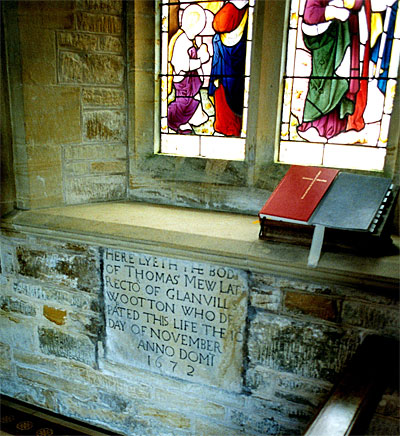 This monument reset in the south wall of the chancel to Thomas Mew, 1672, rector. It is a plain stone slab with bold Roman lettering.