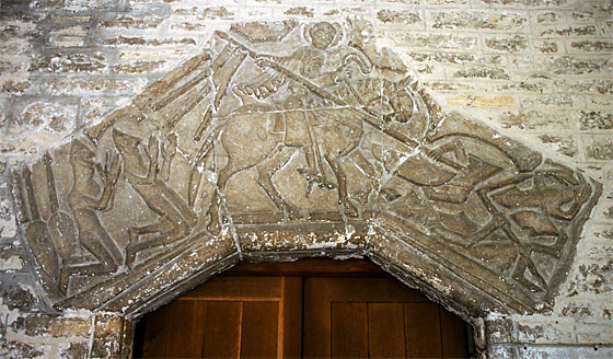 The Tympanum over the door is of great antiquity, and may have been given to the church by William Belet, who was rewarded with the manor of Fordington by William the Conqueror. It is recorded that Belet went on the first Crusade. It would seem he was being hard pressed by the Saracens at the Battle of Dorylaeum 1097, when St. George came to his aid. He and his Squire have fallen to their knees in thankfulness. There are some small differences in the armour of the two groups.