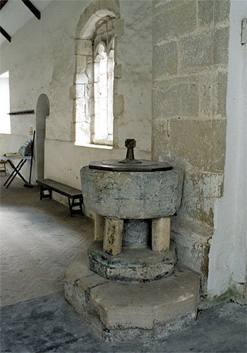 The early 13th century font is of Purbeck marble.