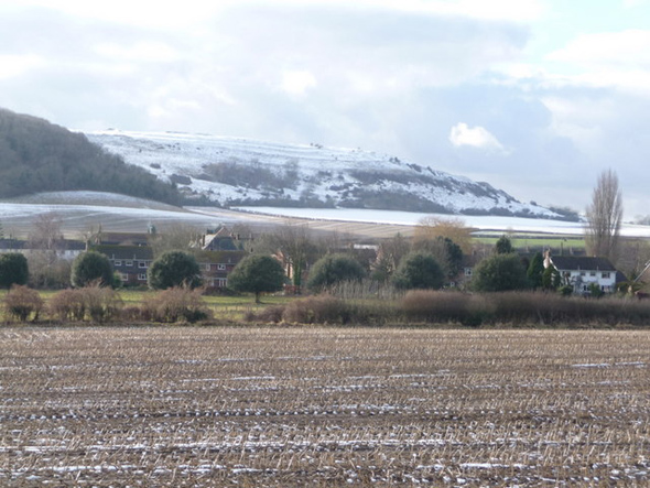 The snow-covered slopes of Hambledon Hill provide a dramatic backdrop to this view of the buildings of Iwerne Courtney village, seen from the A350 which runs parallel to the village's main street. Photo by Chris Downer - for more about Chris Downer click on photo.